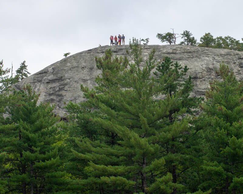 Photo taken looking up at a group of people standing on a giant boulder called Jockey Cap.